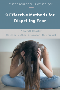 Woman sitting on the floor holding her head in her hands while struggling with dispelling fear.